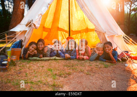 Children smiling in teepee at campsite - Stock Photo
