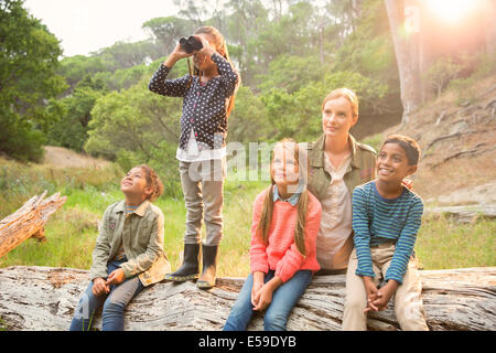 Students and teacher using binoculars in forest - Stock Photo