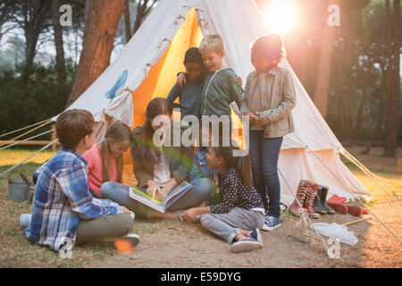 Teacher and students reading at campsite - Stock Photo