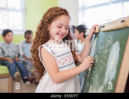 Student drawing on chalkboard in classroom - Stock Photo