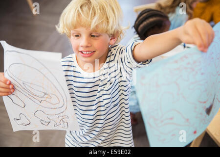 Student showing off drawings in classroom - Stock Photo