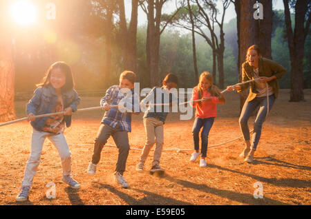 Students and teacher playing tug of war in forest - Stock Photo