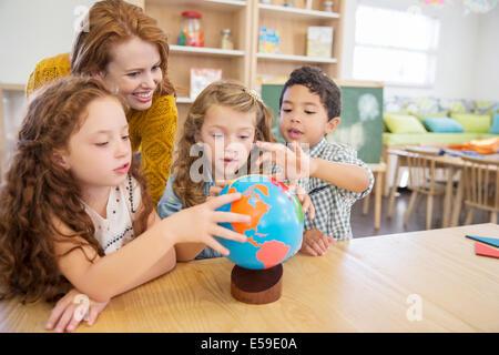 Students and teacher examining globe in classroom - Stock Photo