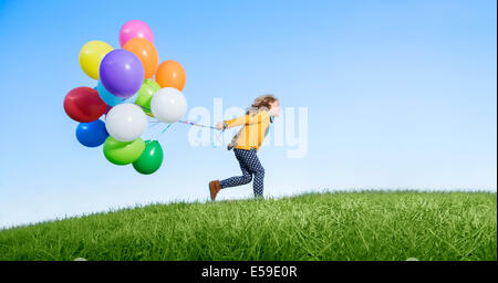 Girl playing with balloons on grassy hill - Stock Photo