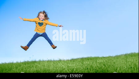 Girl jumping for joy on grassy hill - Stock Photo
