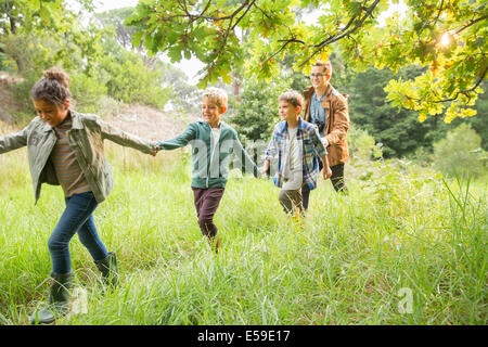 Students and teacher walking outdoors - Stock Photo