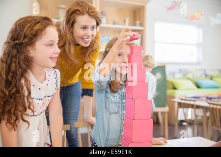 Students and teacher stacking blocks in classroom - Stock Photo