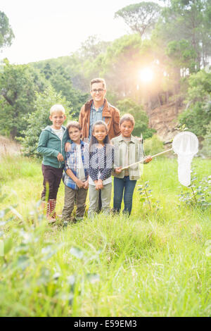 Students and teacher smiling in field - Stock Photo