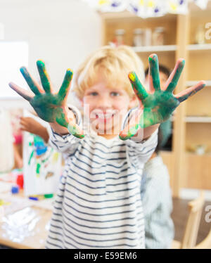 Student showing off messy hands in classroom - Stock Photo
