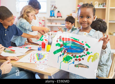 Student showing off finger painting in classroom - Stock Photo