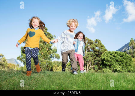 Children holding hands in field - Stock Photo