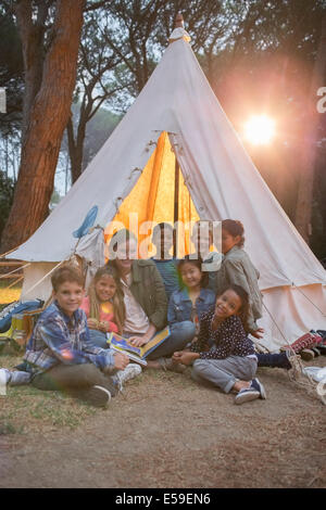 Teachers and students smiling at campsite - Stock Photo