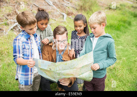 Students and teacher reading map outdoors - Stock Photo