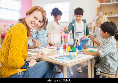 Teacher and students painting in classroom - Stock Photo