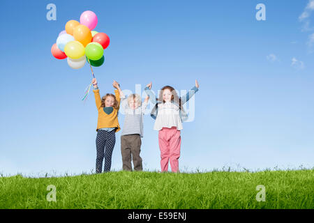 Children with balloons cheering on grassy hill - Stock Photo