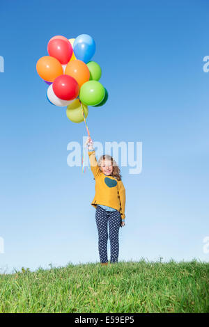 Girl holding bunch of balloons on grassy hill - Stock Photo