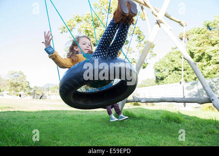 Children playing on tire swings - Stock Photo