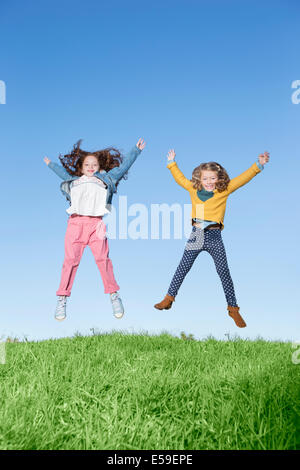 Girls jumping for joy on grassy hill - Stock Photo