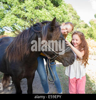 Mother and daughter petting horse outdoors - Stock Photo