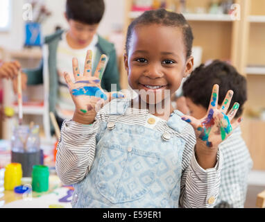 Student with messy hands in classroom - Stock Photo