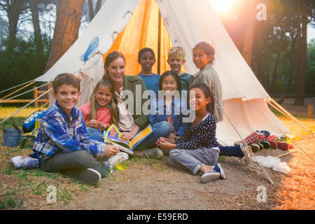 Students and teacher smiling at campsite - Stock Photo
