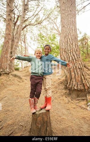 Children climbing on stump in forest - Stock Photo