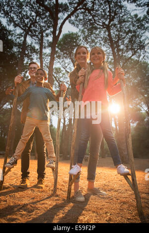 Teachers helping students walk on stilts outdoors - Stock Photo