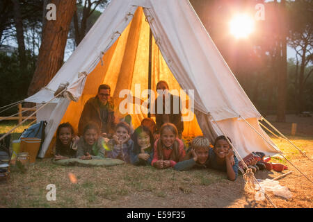 Students and teachers smiling in teepee at campsite - Stock Photo