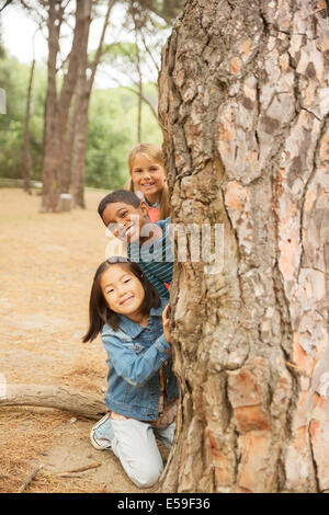 Children peeking out from behind tree in forest - Stock Photo