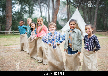 Children smiling at start of sack race - Stock Photo