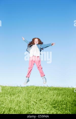 Girl jumping for joy on grassy hill - Stock Photo