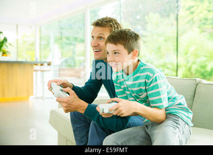 Father and son playing video games in living room - Stock Photo