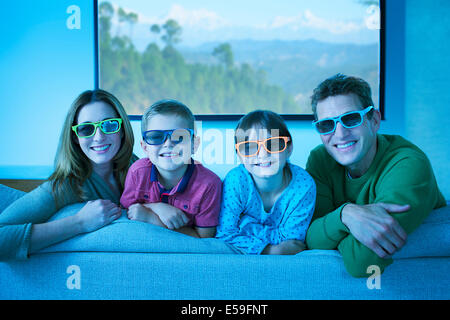 Family wearing 3D glasses in living room - Stock Photo