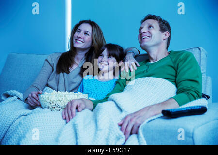 Family watching television in living room - Stock Photo