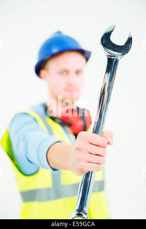 Construction worker holding large wrench - Stock Photo