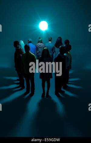 Group with backs to bright light - Stock Photo