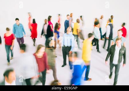 Businessman standing among bustling crowd - Stock Photo