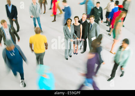 Portrait of business people among bustling crowd - Stock Photo