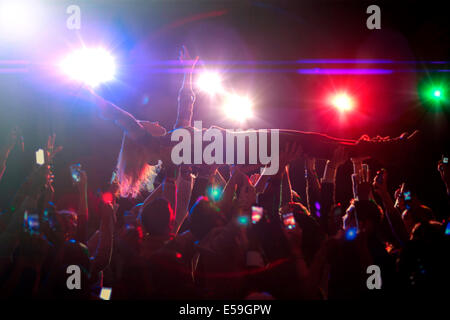 Woman crowd surfing at concert - Stock Photo