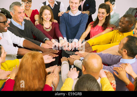 Business people with arms outstretched in huddle - Stock Photo