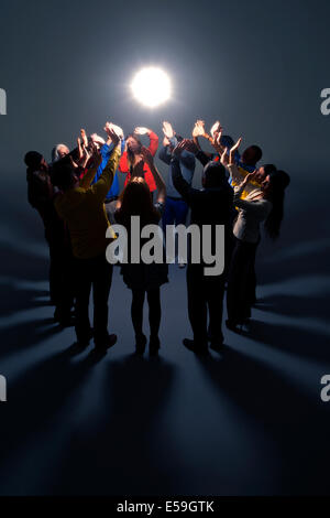 Business people shielding eyes from bright light - Stock Photo