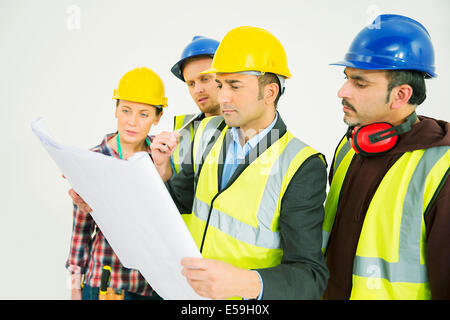Construction workers viewing blueprints - Stock Photo