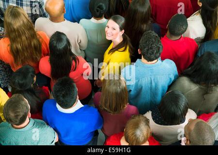 Portrait of confident businesswoman in crowd - Stock Photo
