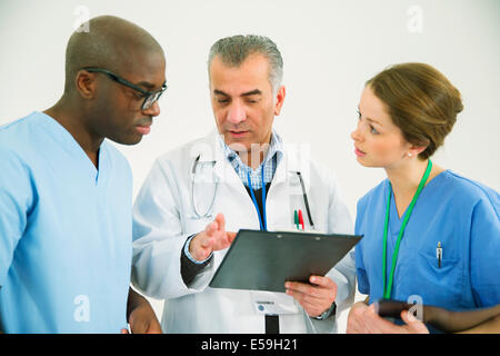 Doctor and nurses with clipboard - Stock Photo