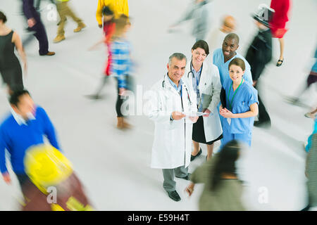 Portrait of confident doctors and nurses among crowd - Stock Photo