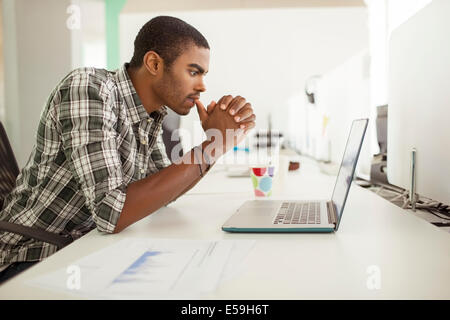 Man working on laptop at office - Stock Photo