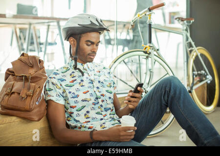 Man in bicycle helmet using cell phone in office - Stock Photo