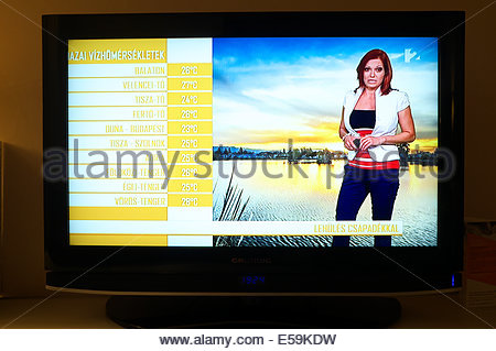 Television weather presenter giving the forecast for Hungary, showing the expected temperatures for different parts - Stock Photo