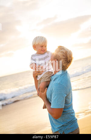 Happy loving father and son on the beach at sunset - Stock Photo