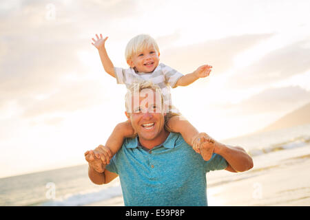 Father holding son on his shoulders on the beach at sunset. - Stock Photo